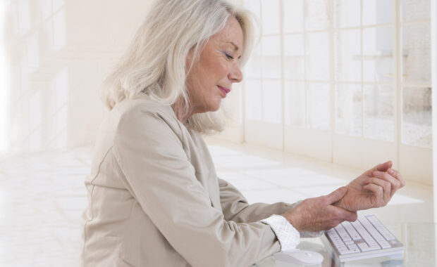 Woman with arthritis pain in her wrist at a computer keyboard
