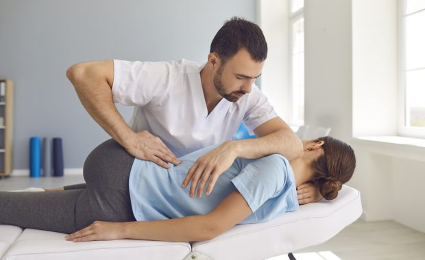 male doctor with patient doing manipulative therapy